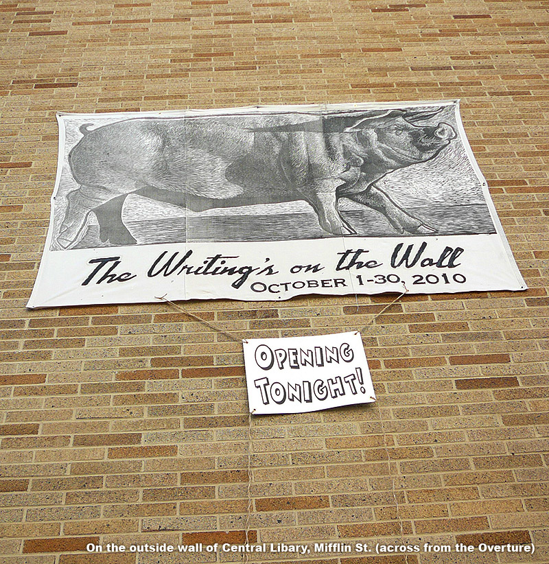 banner on side of building shows 8ft. woodcut print of hog and title: 'The Writing's on the Wall'