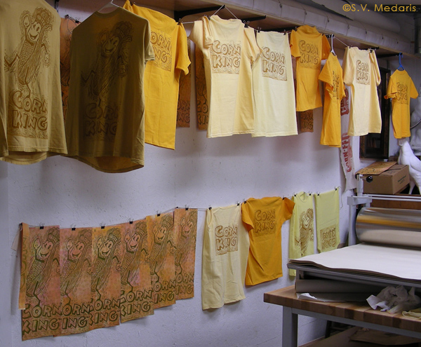 shirts and prints hang drying from line