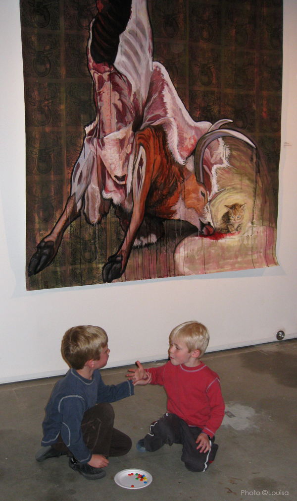 boys eat m&ms in front of painting of hanging deer carcass