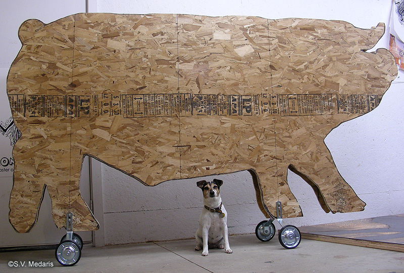 small dog poses in front of 8ft long pulltoy pig cutout