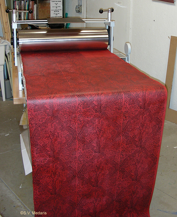 red patterned paper being printed on etching press