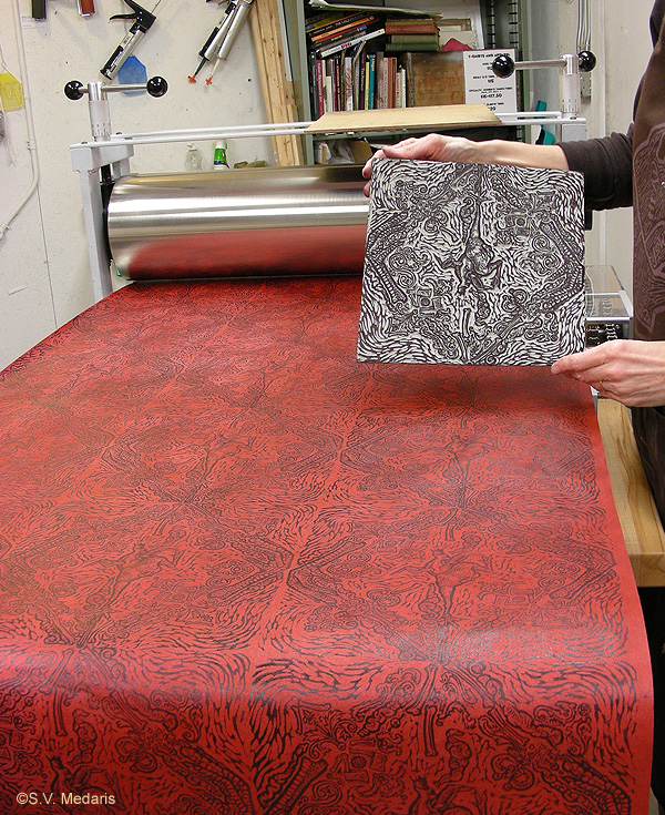 lino block held up for camera. Patterned wallpaper created by this block in background