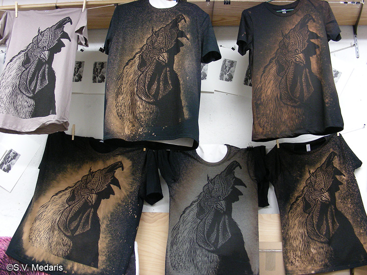 black tees with bleached out woodcut of broiler chicken's head and shoulders