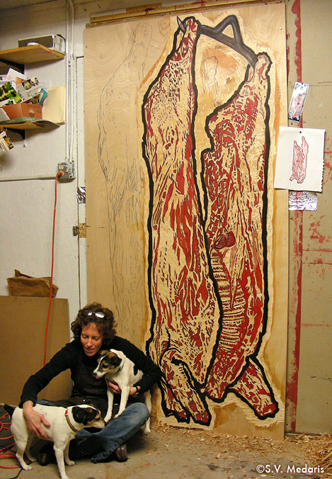 2 little dogs pose in front of 8x4ft sheet of plywood with carcass carved on it