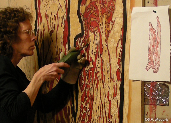 closeup of artist carving large block with electric gouge