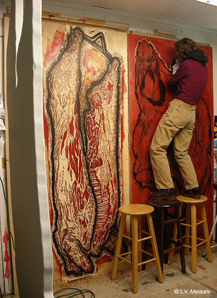 woman stands on stools to carve near the top of an 8ft plywood wood block