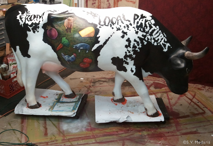 lifesize fiberglass cow painted with wisconsin-made products decorated on it's Holstein body. State of Wisconsin pattern on side of cow.