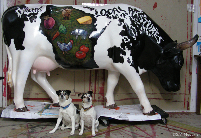 2 little terriers sit before a lifesize fiberglass cow painted with wisconsin-made products decorated on it's Holstein body. State of Wisconsin pattern on side of cow.