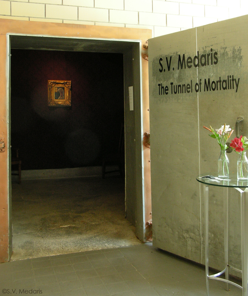 Door's entrance to old cheese cooler with show title: S.V. Medaris, The Tunnel of Mortality, inside reveals dark, wallpapered room.