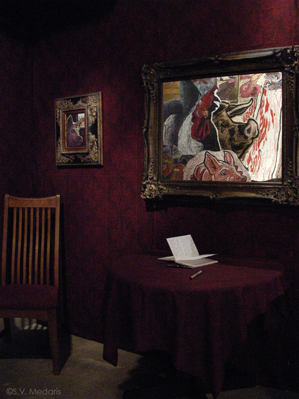 Fancy framed portraits on dark wallpapered walls, and low table covered in matching tablecloth