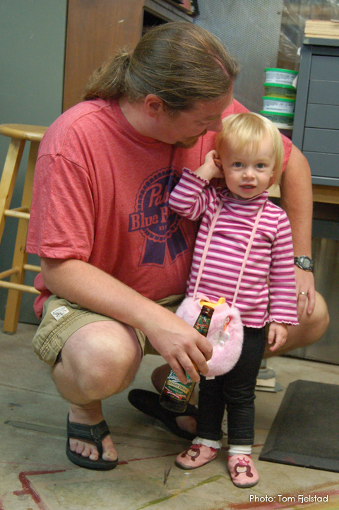 Young girl in pink with pink furry purse, stands with Dad