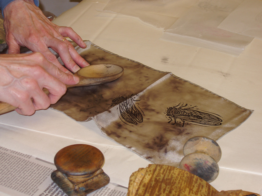 hands use wooden spoon to rub/transfer ink from block onto mottled brown silk fabric