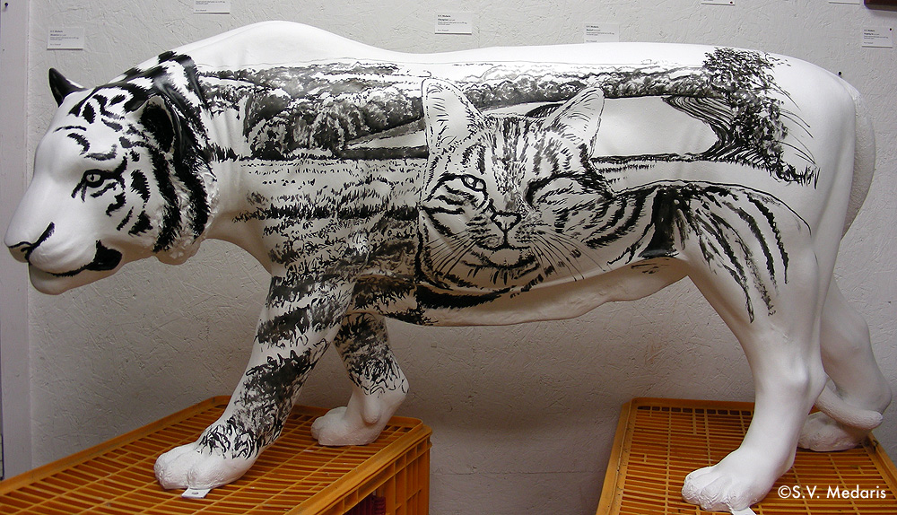 Black line painting of tiger cat (tabby) on side of white, fiberglass tiger
