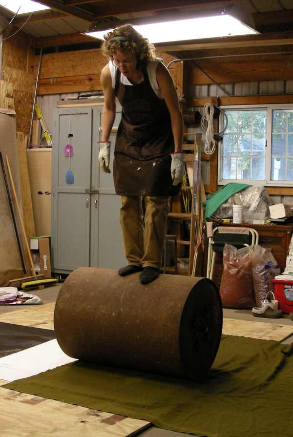 woman stands on top of barrel on top of blanket-covered plywood